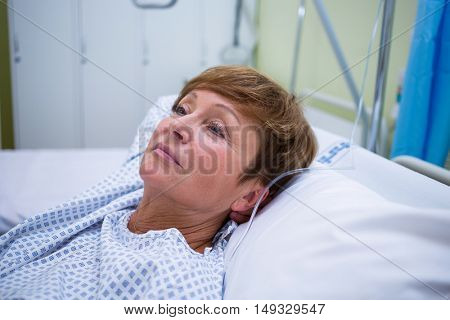 Sad senior patient lying on a bed in hospital room
