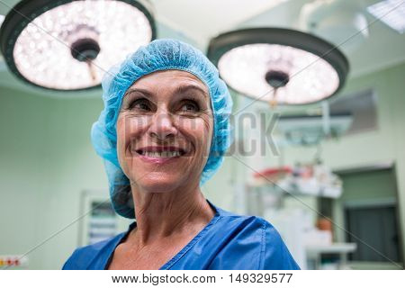Smiling surgeon standing in operation room at hospital