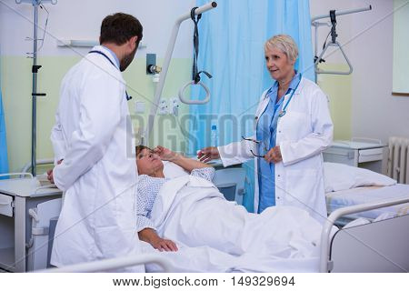 Doctors talking to a senior patient in hospital room