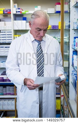 Pharmacist holding a prescription and medicine in pharmacy