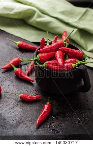 Food and drink, still life, moody concept. Raw red mexican chili peppers on a black rusty table. Selective focus