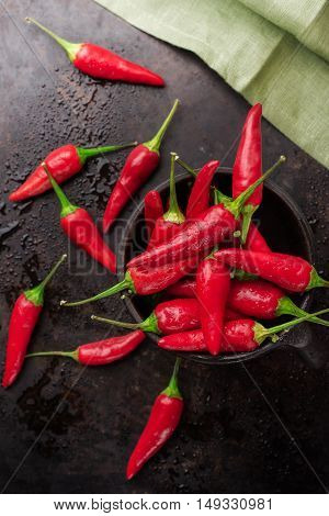 Food and drink, still life, moody concept. Raw red mexican chili peppers on a black rusty table. Selective focus top view flat lay