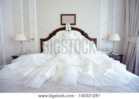 Beautiful white wedding dress and shoes for bride indoors. Beauty of bridal gown for marriage. Female lace clothes for celebration