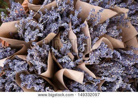 Top view on beautiful fresh lavender flowers in the basket on the street market. Bunches of lavender in craft paper. Romantic flowers.
