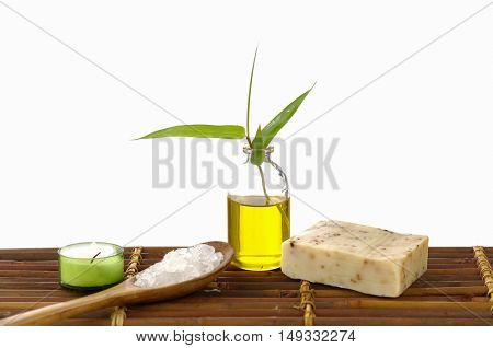 massage oil and leaf, with Salt in spoon ,soap, candle on bamboo mat
