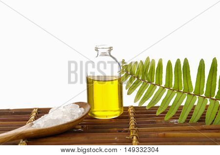 massage oil and fern with Salt in spoon on bamboo mat