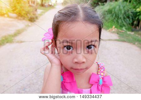 Portrait of a cute preschool girl with flower over ear