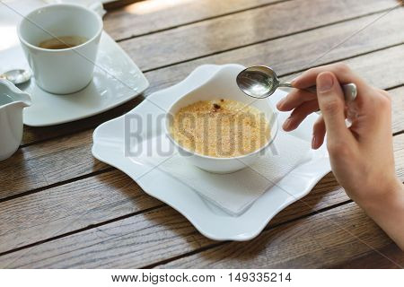 Dessert creme brulee in white plate and hand with spoon. The concept of temptation, fun, sweets, French cafe