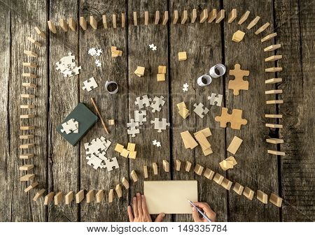 Top down view of dominos and puzzle pieces over wooden planks. Hand of writer with pen and notepad.