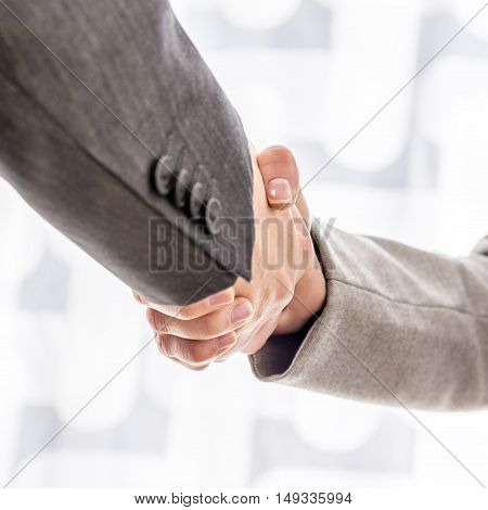 Business man and woman in formal attire shaking hands on a deal over a high key background close up oblique angle view.
