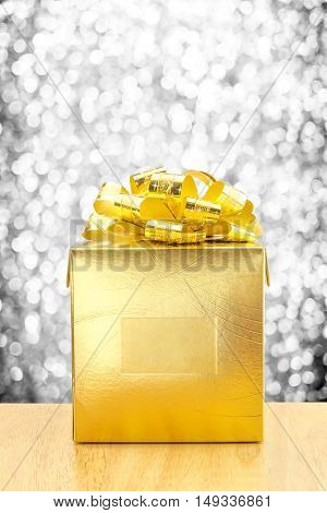 Golden Present Box At Silver Bokeh Light Background, Leave Space For Adding Your Text