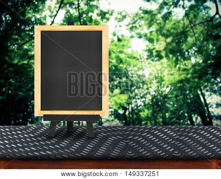 Blackboard Menu With Easel On Black Fabric Table With Blur Tree Background, Copy Space For Adding Yo
