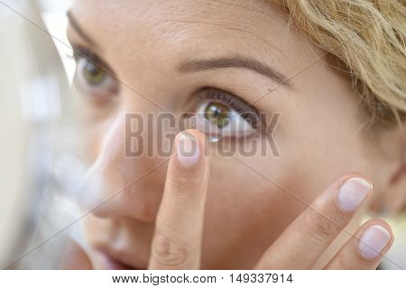 Woman putting lenses on