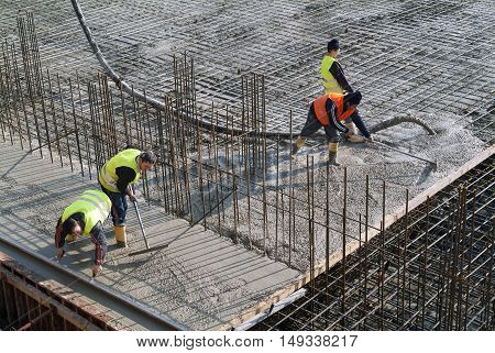 Milan, Italy - January 17, 2016 - Concrete casting on Reinforcing Bar of floor in industrial Construction site
