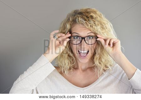 Portrait of blond woman with eyeglasses being cheerful