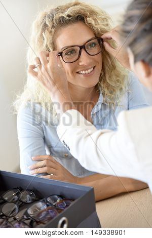 Blond woman at the optical shop, trying eyeglasses on
