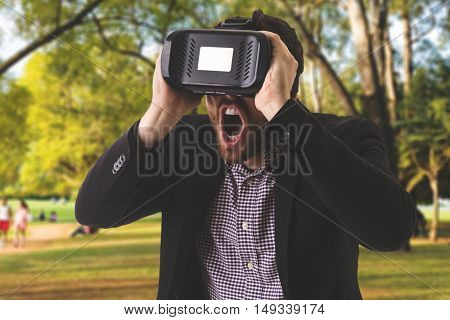 Attractive man with virtual reality glasses in the park