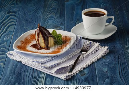 poached pear with syrup on plate and coffee cup