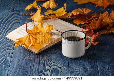 Cup Of Tea Wit Old Book And Autumn Leaves On Wooden Table
