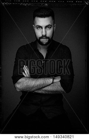 Handsome bearded man wearing shirt, portrait shot in studio, black and white photo