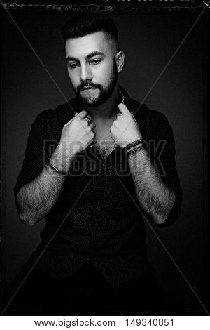 Handsome bearded man wearing shirt, portrait shot in studio, black and white photo