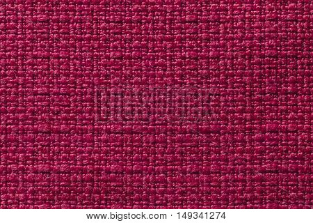 Dark red background from a textile material. Fabric with natural texture. Cloth backdrop.