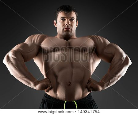 Handsome muscular bodybuilder posing over black background. Concept of the sport, strong, healthy lifestyle and nutrition.