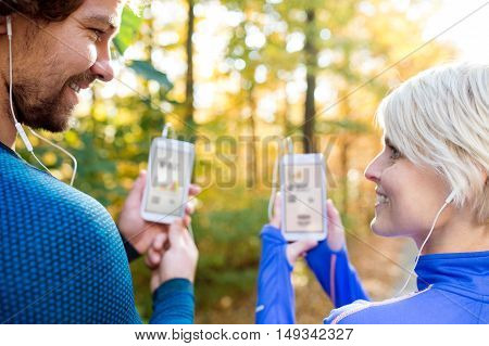 Beautiful couple running together outside in colorful sunny autumn forest using a fitness app on their smartphones. Using phone app for tracking weight loss progress, running goal or summary of their run. Rear view.