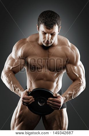 Portrait of bodybuilder with dumbbells in his arms on grey background in a studio. Isolated with clipping path.