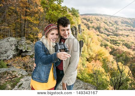Beautiful young couple on a walk, standing on a rock against colorful autumn forest, woman holding binoculars, pointing at something with her finger
