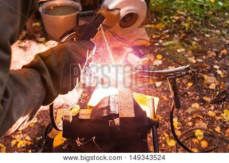 Welder Welds Iron Ring Outdoors