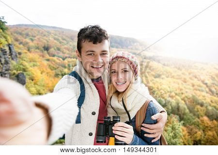 Beautiful young couple on a walk in sunny autumn forest taking selfie, woman holding binoculars