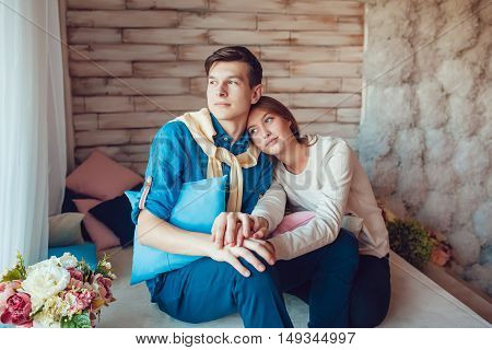 Young couple embracing sitting at home and looking out the window