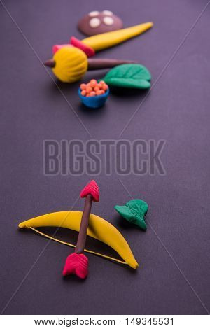 happy dussehra, happy aayudha pooja or puja or happy vijayadashami greeting card made using photograph of clay model of arms like bow and arrow, sword / shield, gadda or gada and sweets with apta leaf