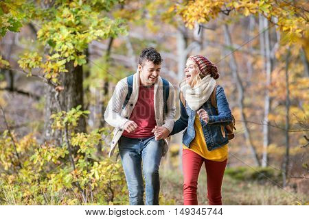 Beautiful couple on a walk in colorful sunny autumn forest, running and laughing.