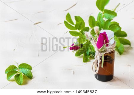 Rose essential oil in a glass bottle on a light table. Used in medicine cosmetics and aromatherapy. Fresh flowers and green leaves.