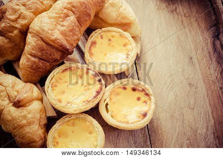 Egg tarts and croissants on a wooden table - tone vintage