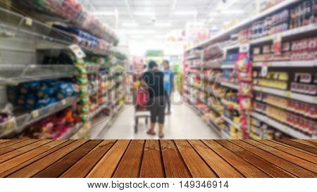 Wooden plank and people walking select products in the supermarket blur.