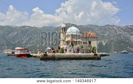 Perast, Montenegro - June 27th 2016. Tourists visit the tiny man-made island of Ou Lady of the Rock off the coast of Perast in Kotor Bay at the stat of the tourist season.