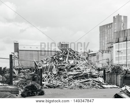 Large Metallic waste solution dump pile in the yard of a factory with big furnace and processing unit in the background