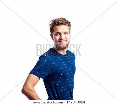 Hipster man in striped blue t-shirt, arm on hip, studio shot on white background, isolated