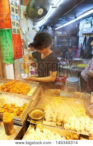 HONG KONG - 25 DECEMBER 2015: worker of street cafe in Kowloon at night. Kowloon is an area in Hong Kong comprising the Kowloon Peninsula and New Kowloon.