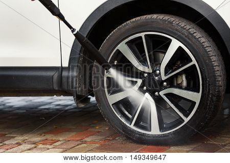 car wheel washing with high pressure washer