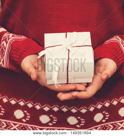 Woman in red sweater holding christmas giftbox with red and white ribbon