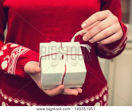 Hands of girl in red sweater holding a cristmas gift box with red and white ribbon