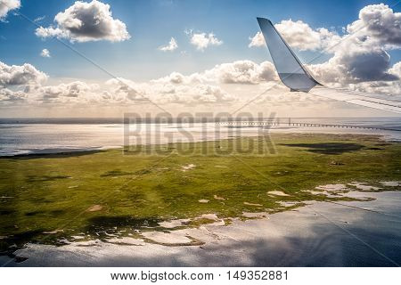 Wing of an airplane flying above Oresund Bridge in Denmark. Clouds and landscape under the wing of the aircraft.