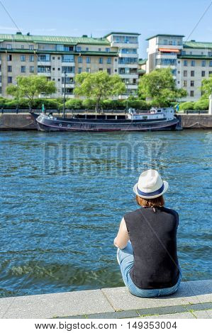 Girl in hat sitting on pier and lookingat the river