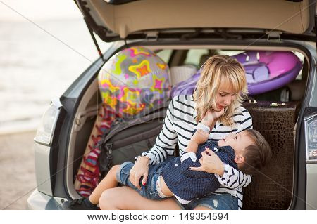Beautiful woman with a child of four years in the car are going to have a trip