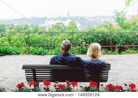 Happy ssenior couple sitting on bench and talking in the park