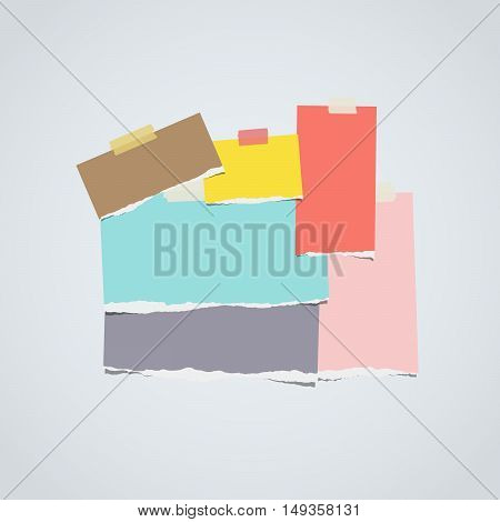 Ripped colorful notebook, note paper stacked on gray background.